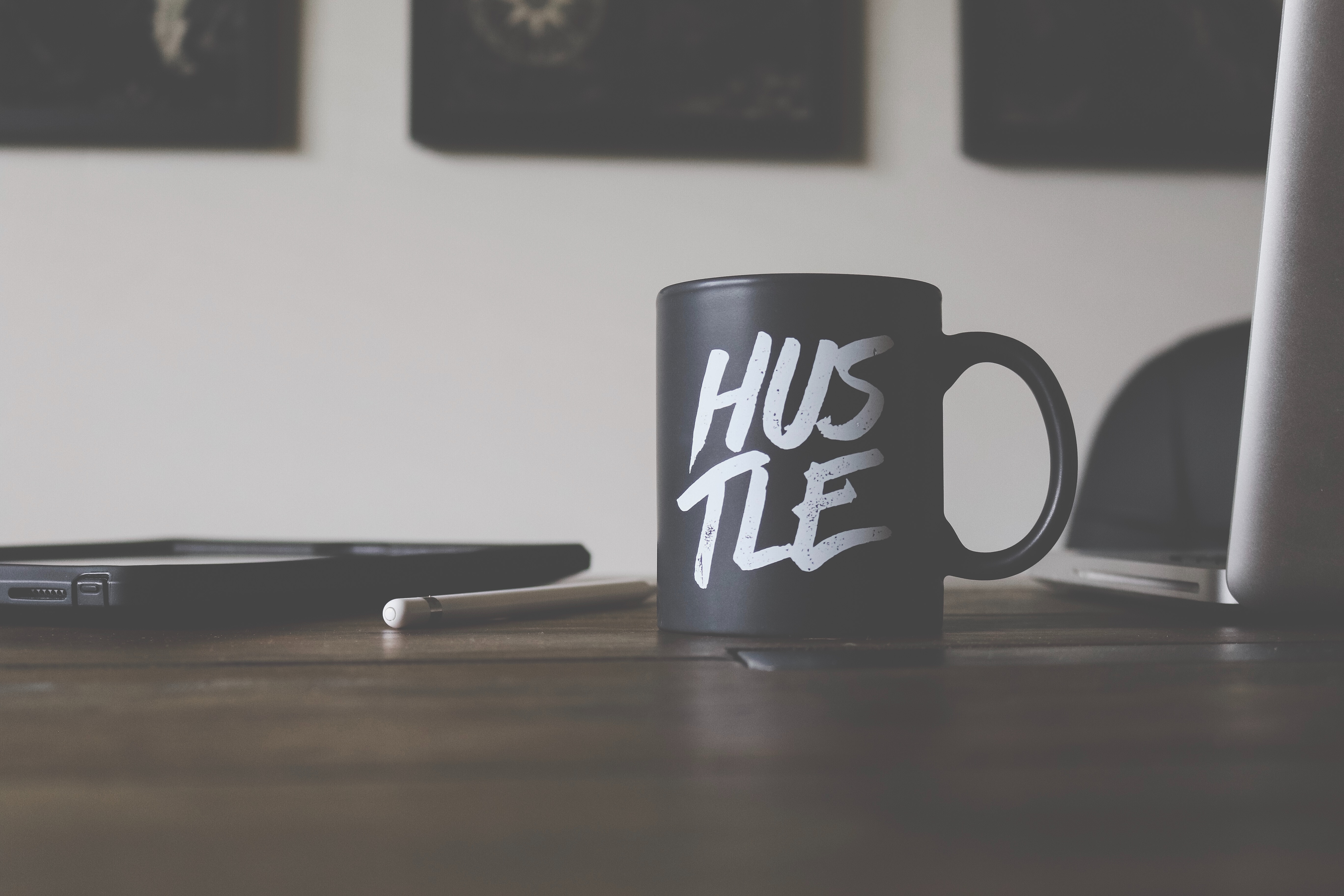 A black coffee mug with the word 'Hustle' printed on it, sitting on a desk by a laptop and a pencil.