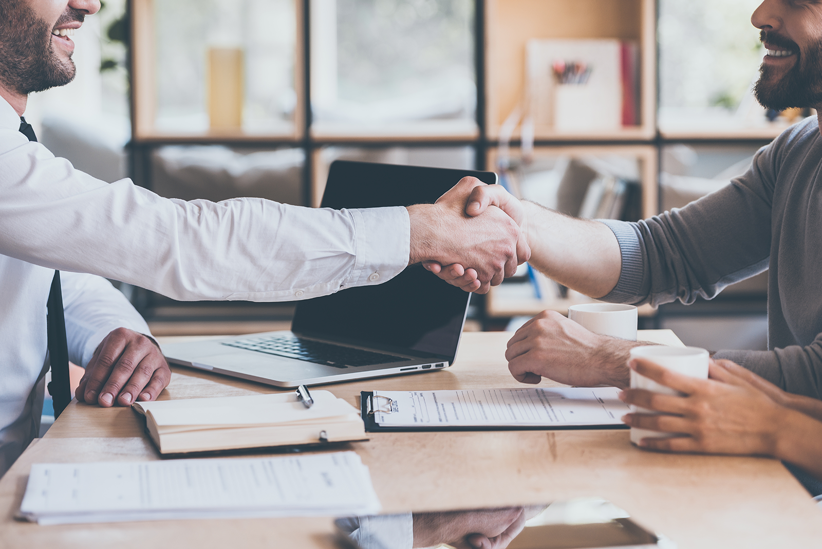 two men shake hands after securing business investment