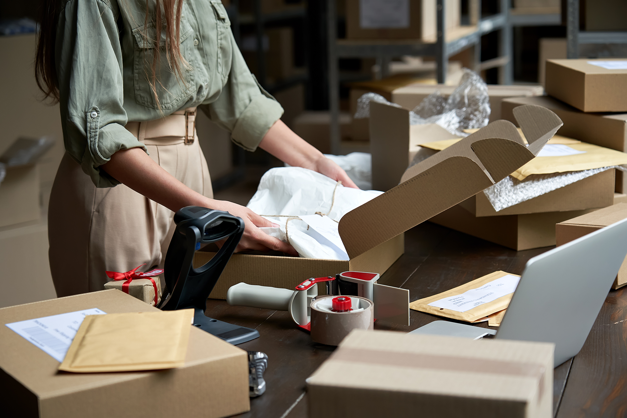 a women uses the best ecommerce platform to run her small business, packing boxes on a table