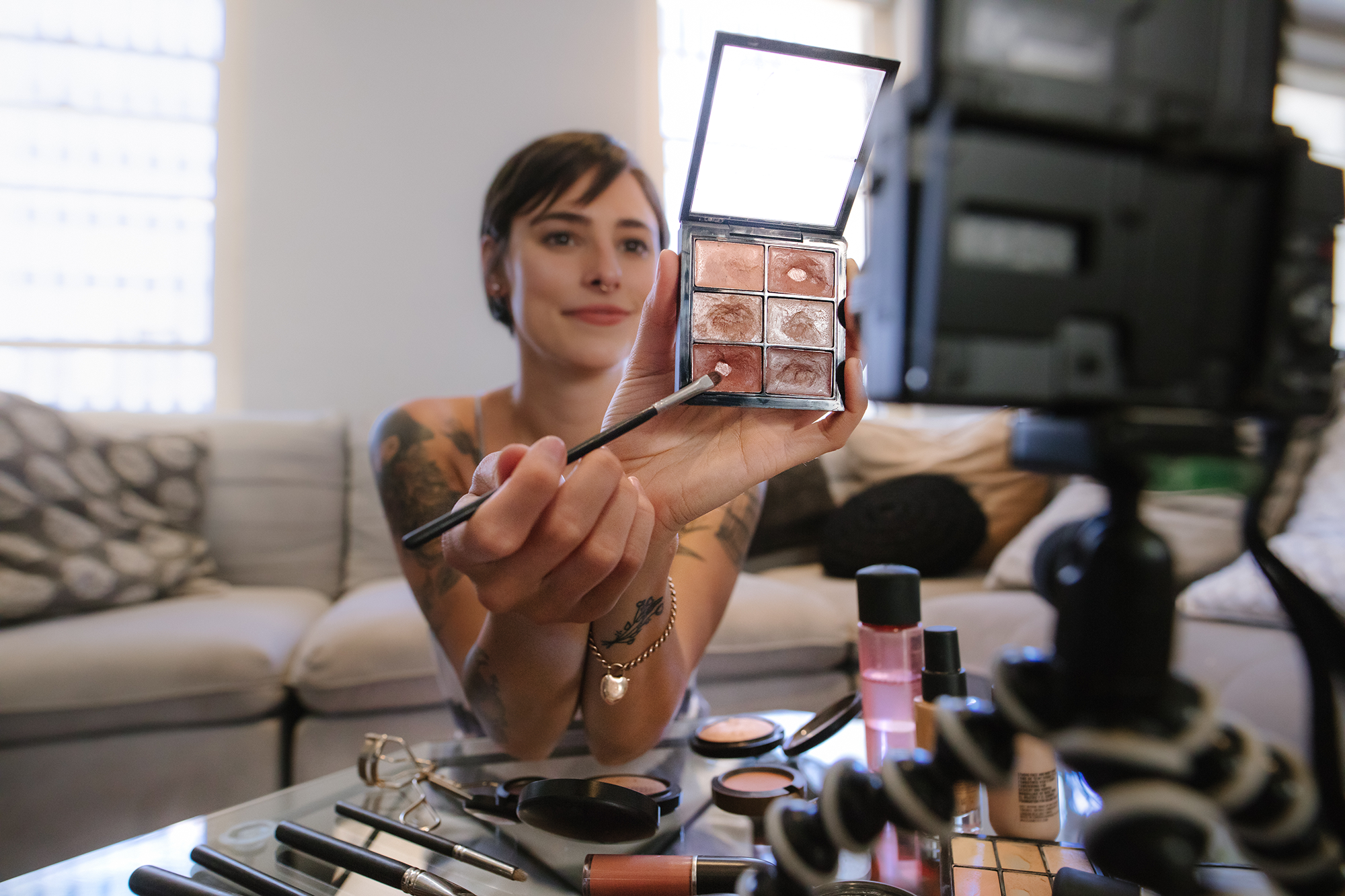 A tattooed woman shows a makeup palette on YouTube