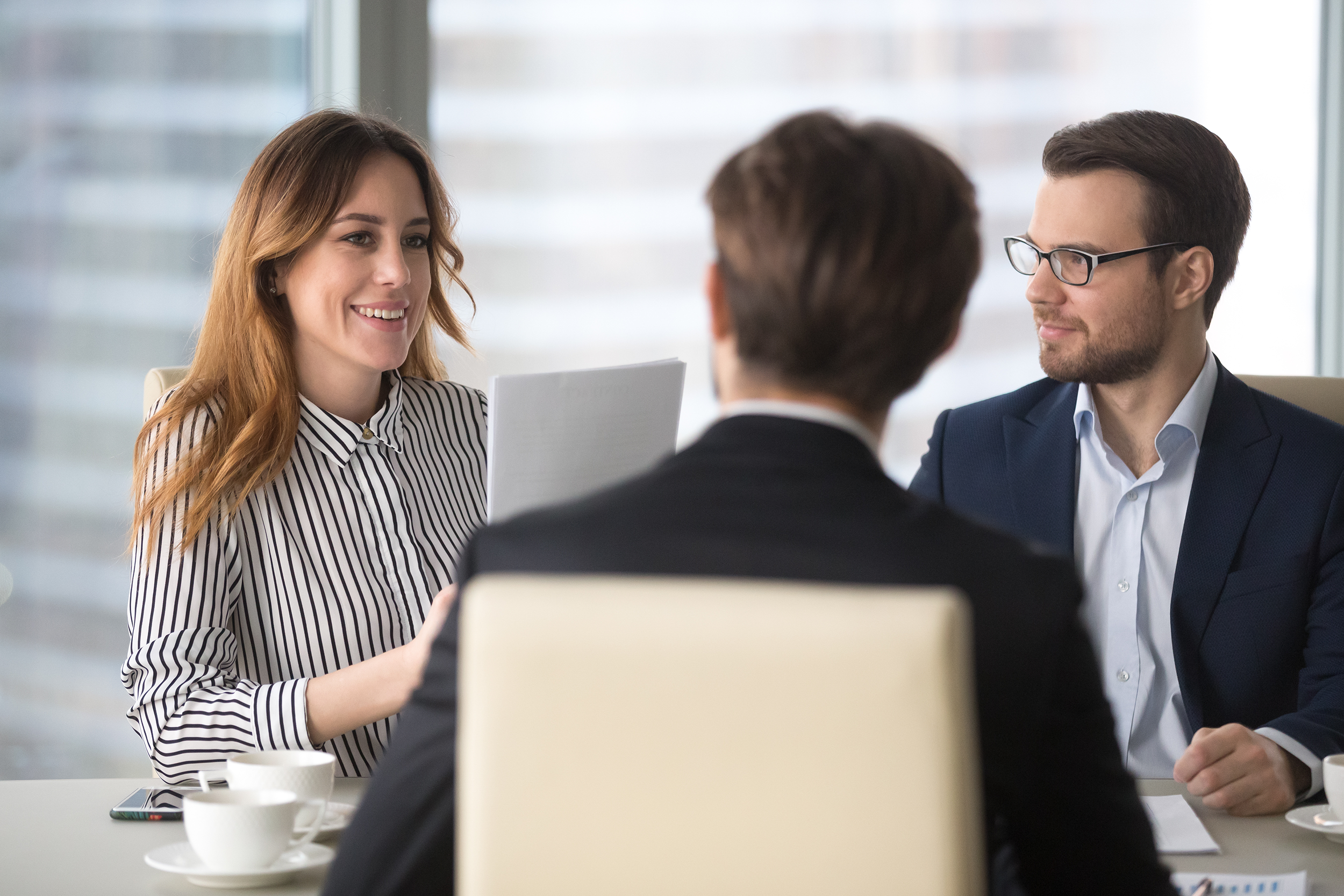A woman delivers her companies value proposition in a meeting with two businessmen