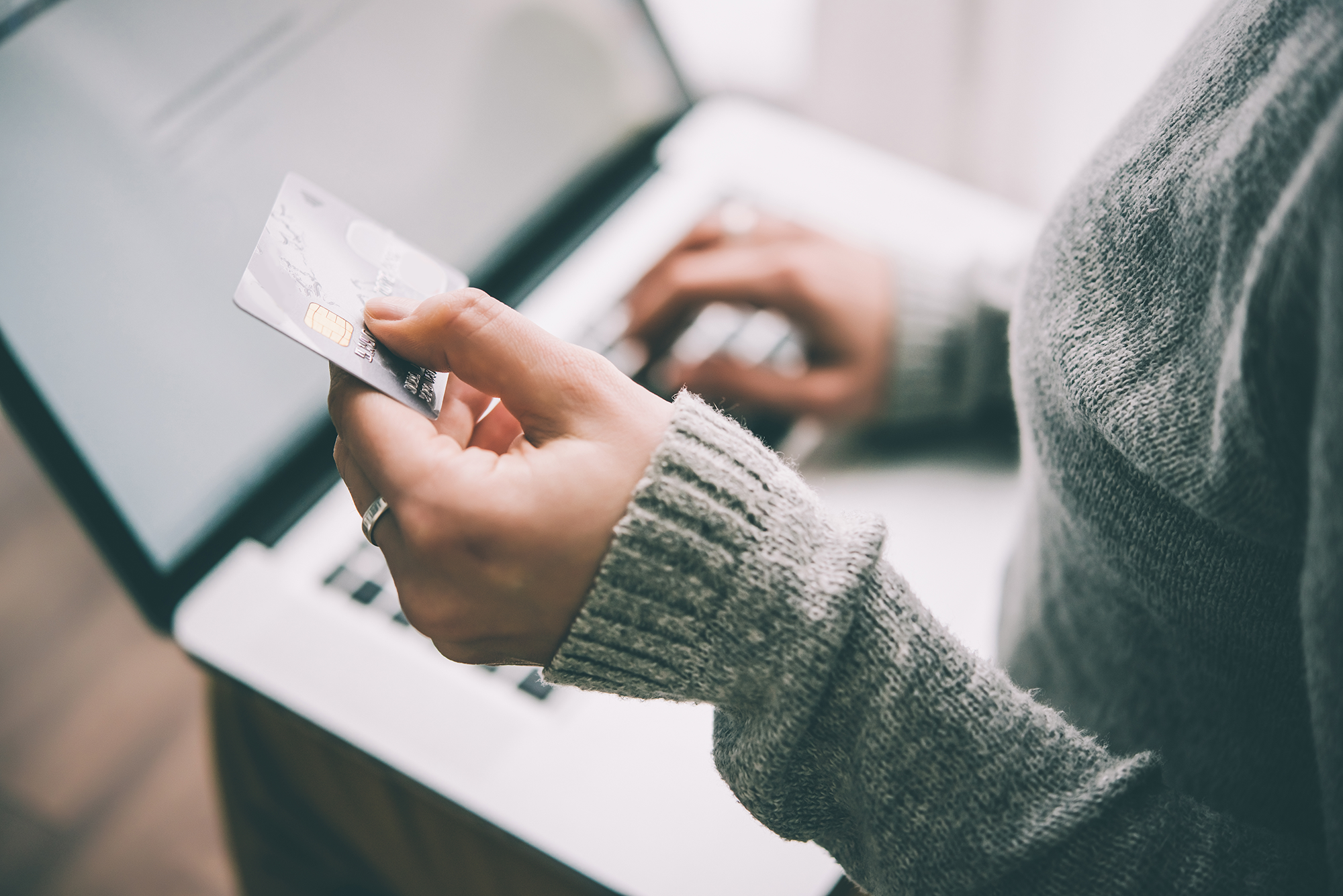 A woman uses a laptp to make a credit card payment online