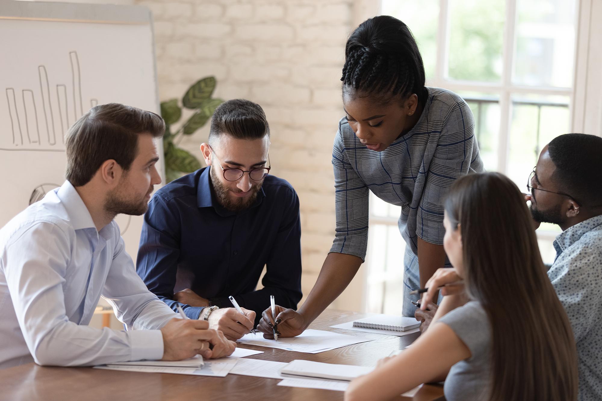 Woman supervisor boss teach diverse staff workers explain partnership agreement paperwork at group meeting